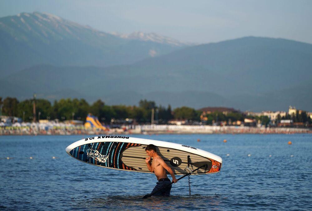 Mężczyzna z deską surfingową w Soczi