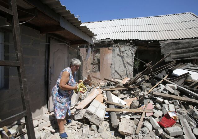 Miejscowa mieszkanka pod domem zniszczonym po ostrzale artyleryjskim w wiosce Marinka pod Donieckiem