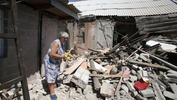 Miejscowa mieszkanka pod domem zniszczonym po ostrzale artyleryjskim w wiosce Marinka pod Donieckiem - Sputnik Polska