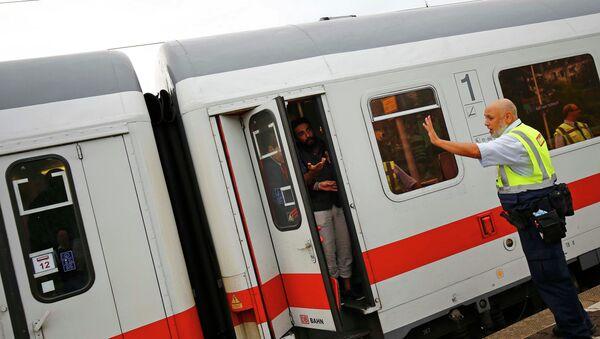 Pracownik niemieckiego przewoźnika kolejowego Deutsche Bahn uniemożliwia imigrantom opuszczenie pociągu na stacji we Frankfurcie - Sputnik Polska