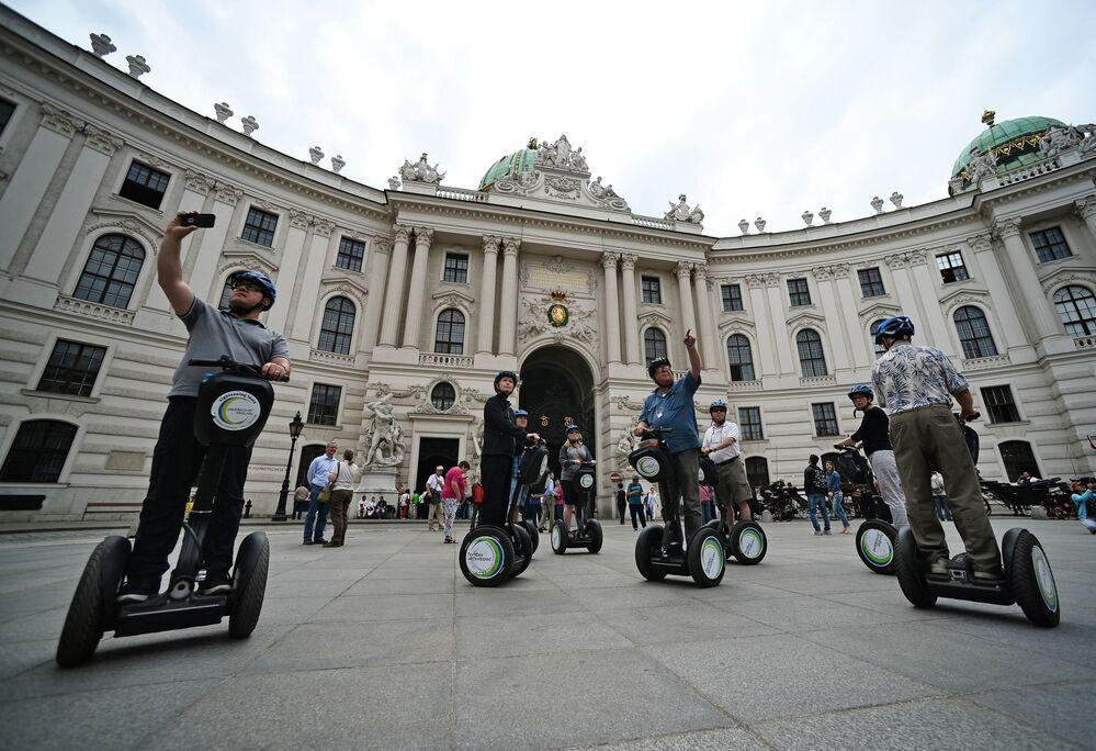 Turyści jeżdżą na segway przy wiedeńskim pałacu władzów Austrii