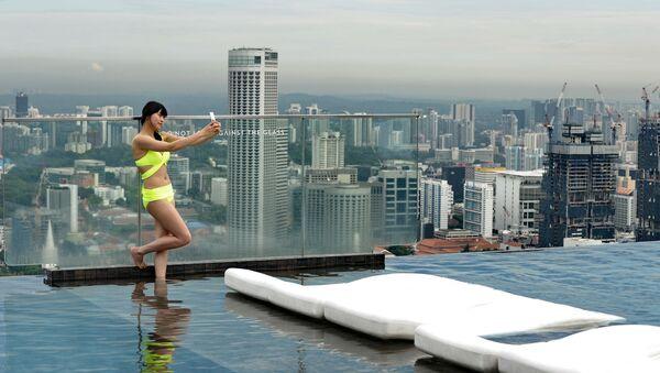 Kobieta robi sobie selfie na dachu hotelu Marina Bay Sands w Singapurze - Sputnik Polska