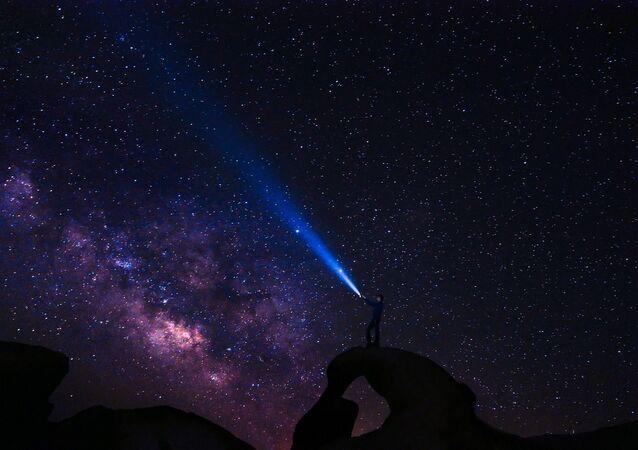 Człowiek z latarką pod rozgwieżdżonym niebem