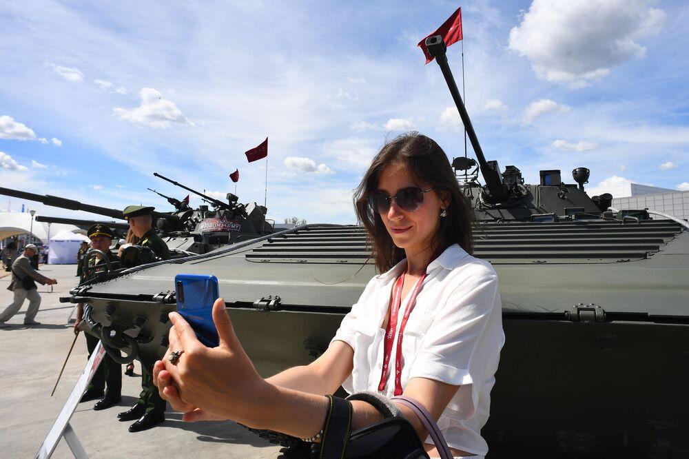 """Kobieta fotografuje się przy radzieckim wozie bojowym piechoty na Międzynarodowym Forum Wojskowym """"Armia-2019"""""""