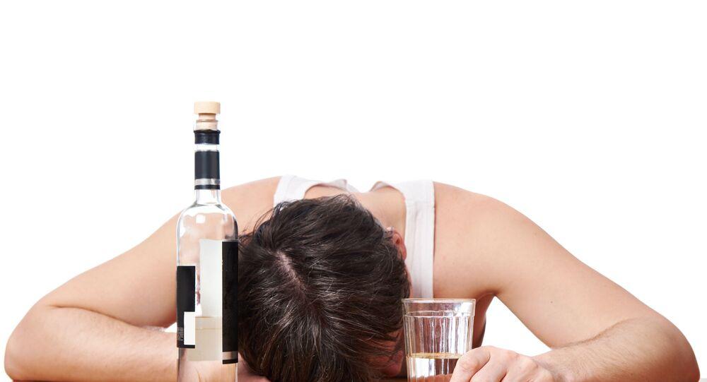 Pijany mężczyzna z butelką wódki.