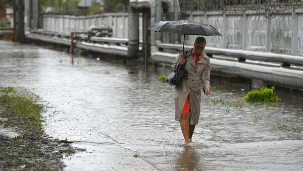 Kobieta idąca podtopioną ulicą w rejonie lotniska Szeremietiеwo - Sputnik Polska