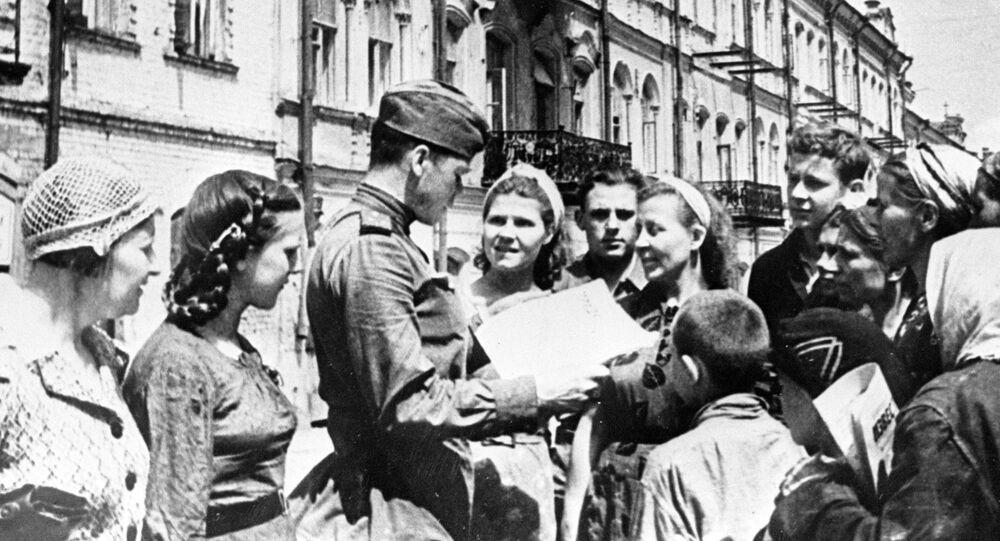 """Radziecki żołnierz pokazuje mieszkańcom wyzwolonego Mińska gazetę """"Prawda"""""""