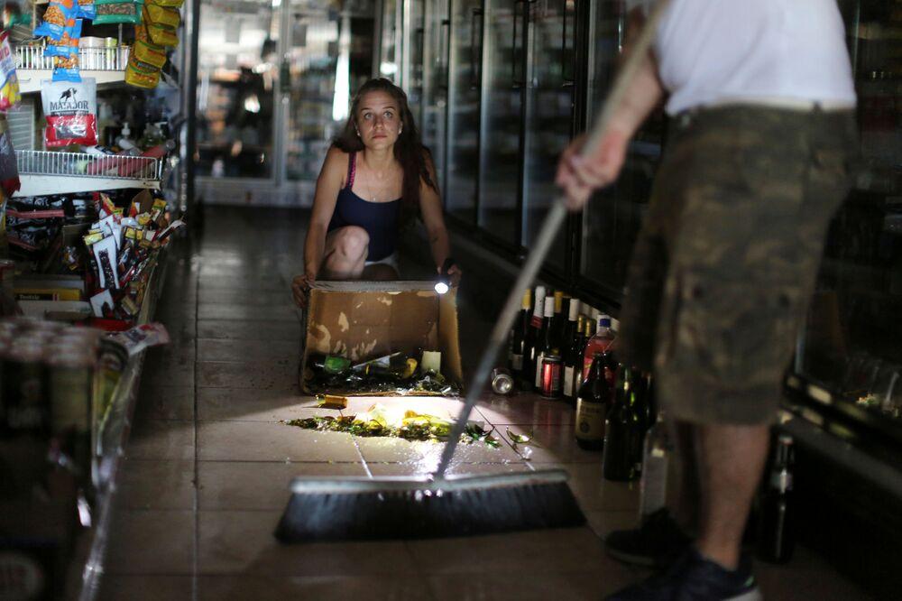 Kaitlin Alexander sprząta porozbijane butelki w supermarkecie.