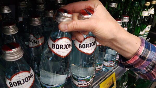 """Kupujący bierze wodę mineralną """"Borjomi"""" z półki w supermarkecie - Sputnik Polska"""