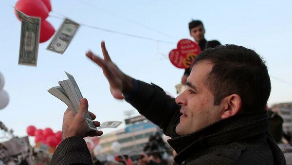 Mężczyzna rozrzuca imitację amerykańskich dolarów na znak protestu przeciwko korupcji w Turcji - Sputnik Polska