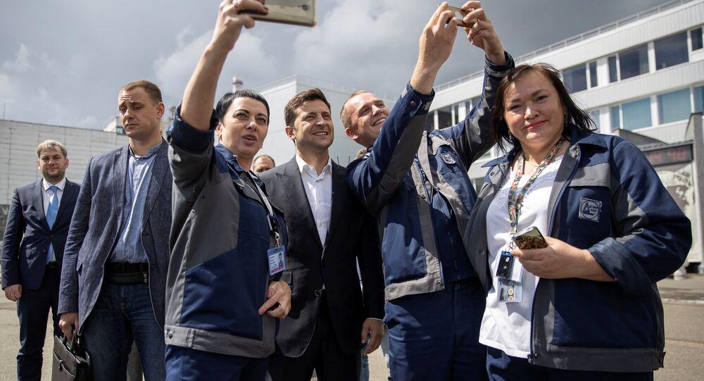 Prezydent Ukrainy Wołodymyr Zełenski robi sobie zdjęcie z pracownikami Czarnobylskiej Elektrowni Atomowej w czasie uroczystości oddania do użytku nowego sarkofagu nad czwartym uszkodzonym reaktorem jądrowym w Czarnobylu.