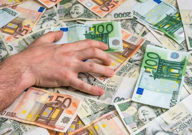 Ręka mężczyzny na banknotach euro i czeskich złotych