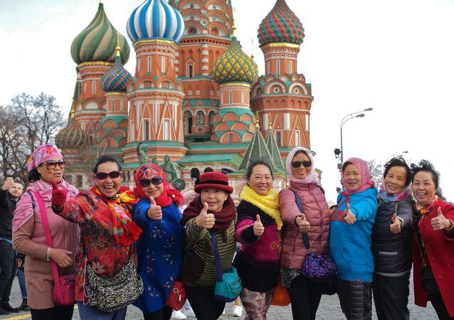 Turyści fotografują się na Placu Czerwonym, na tle Soboru Wasyla Błogosławionego w Moskwie