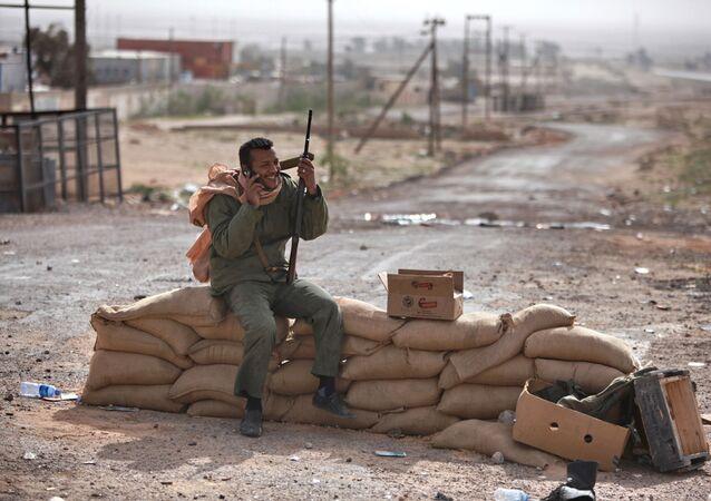 Bojownik z pistoletem rozmawia przez telefon komórkowy we wschodniej części Libii