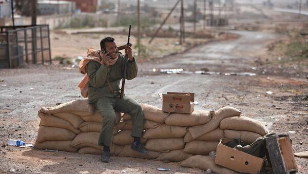Bojownik z pistoletem rozmawia przez telefon komórkowy we wschodniej części Libii - Sputnik Polska