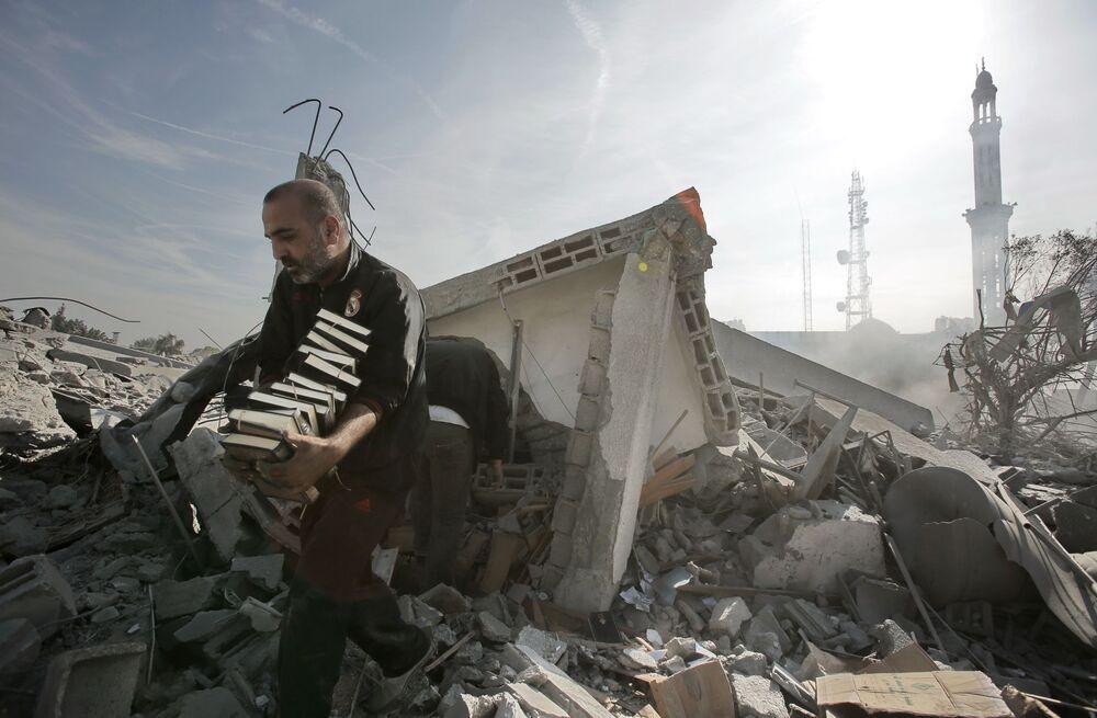Mężczyzna wynosi stosy Koranu z budynku zniszczonego podczas eksplozji w Gazie