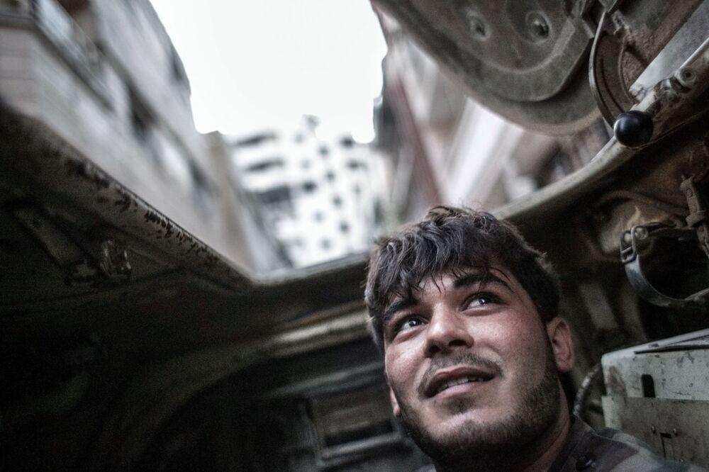 Żołnierz wewnątrz transportera opancerzonego podczas starć z bojownikami w centrum Homs
