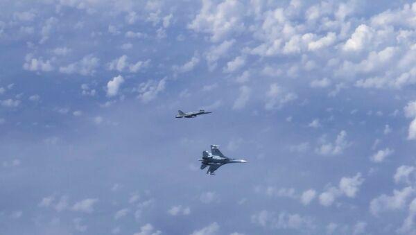 Samolot Su-27 odsuwa F-18, zbliżający się do samolotu Siergieja Szojgu - Sputnik Polska