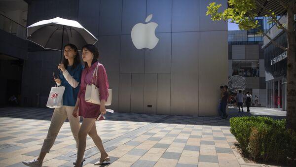 Dziewczyny przechodzą obok sklepu Apple w jednym z centrów handlowych w Pekinie - Sputnik Polska