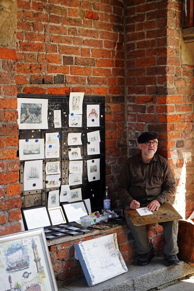 Artysta uliczny ze swoimi obrazami na jednej z ulic Lubeki.