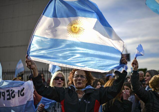 Zwolennicy prezydenta Argentyny Mauricio Macri z flagą Argentyny podczas marszu w Buenos Aires