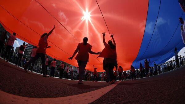 Uczestnicy flash mobu na cześć Dnia Flagi Narodowej Rosji rozwinęli dużą rosyjską flagę na Prospekcie Sacharowa w Moskwie - Sputnik Polska