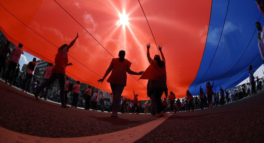 Uczestnicy flash mobu na cześć Dnia Flagi Narodowej Rosji rozwinęli dużą rosyjską flagę na Prospekcie Sacharowa w Moskwie.