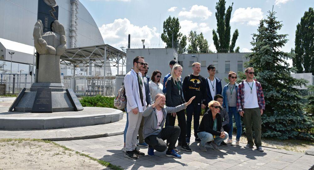 Turyści robią zdjęcia w pobliżu pomnika likwidatorów wypadku w Czarnobylu podczas wycieczki do strefy wykluczenia w Czarnobylu