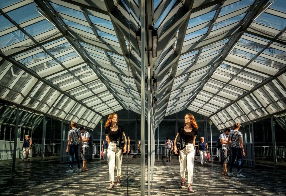 Kobieta idąca przez przejście dla pieszych w centrum Moskwy patrzy na swoje odbicie w lustrze