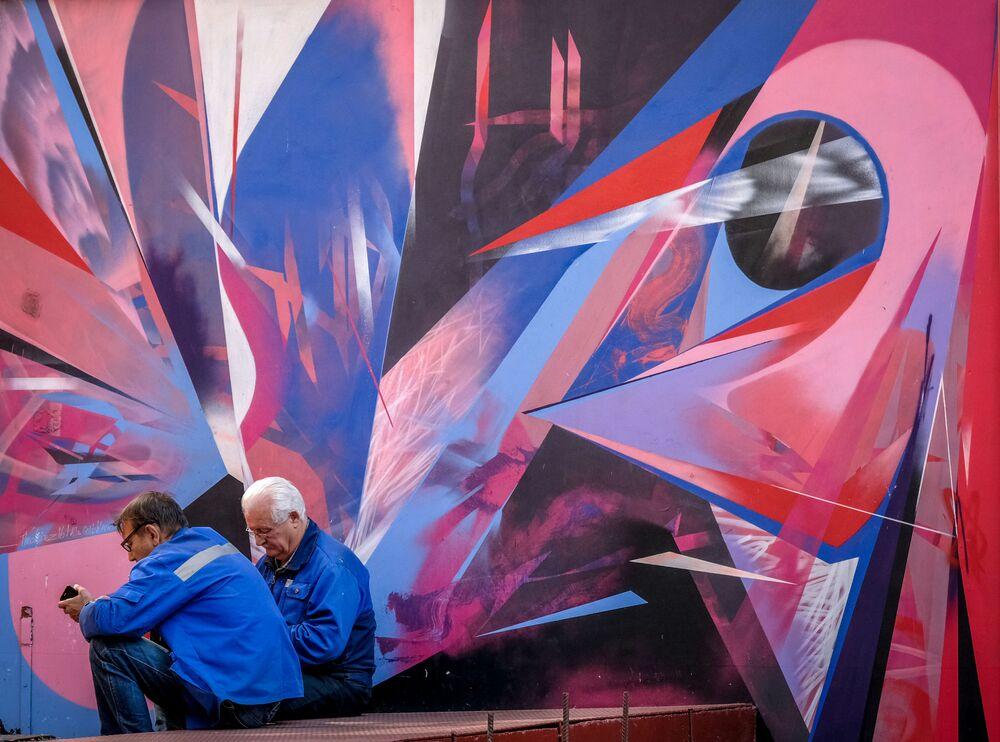 Robotnicy odpoczywają pod blokiem ozdobionym graffiti