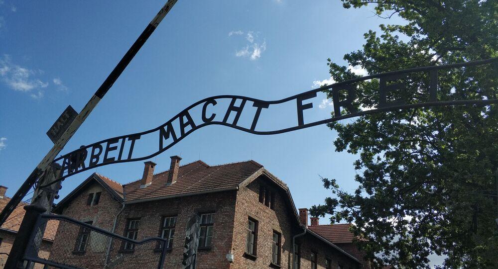 """Niemiecki slogan """"Arbeit macht frei"""" na bramie w Auschwitz"""