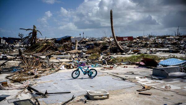 Rowerek dziecięcy na tle zniszczeń po huraganie Dorian w Abaco na Bahamach  - Sputnik Polska