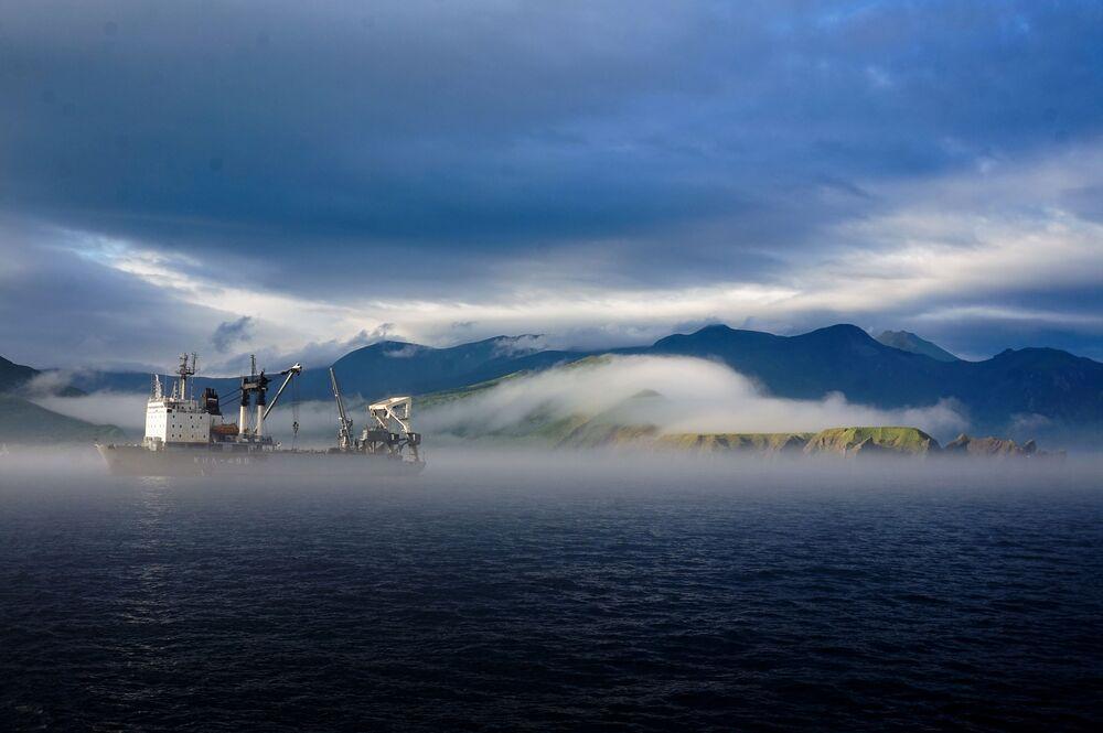 Członkowie wyprawy patrzą na Cieśninę Frieza i wyspę Iturup (w tle) z brzegu wyspy Urup (wyspa południowej grupy Wielkiego Grzbietu Wysp Kurylskich).