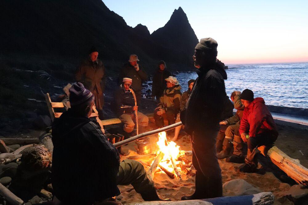 Członkowie wyprawy wokół ogniska na brzegu zatoki Szczukina na wyspie Urup (wyspa południowej grupy Wielkiego Grzbietu Wysp Kurylskich).