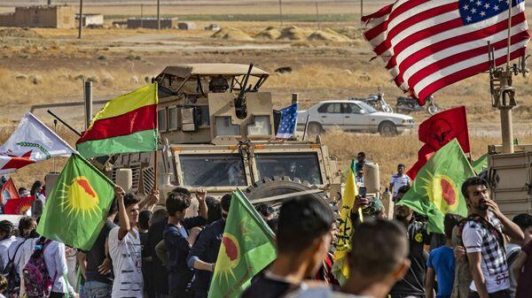 Syryjscy Kurdowie wokół amerykańskich pojazdów opancerzonych podczas demonstracji przeciwko tureckim zagrożeniom w pobliżu bazy wojskowej w syryjskiej prowincji Hasake - Sputnik Polska