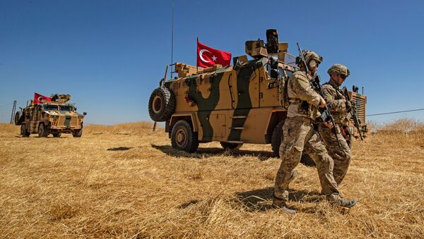 Amerykańscy żołnierze mijają turecki pojazd opancerzony na obrzeżach Tal Abyad - Sputnik Polska