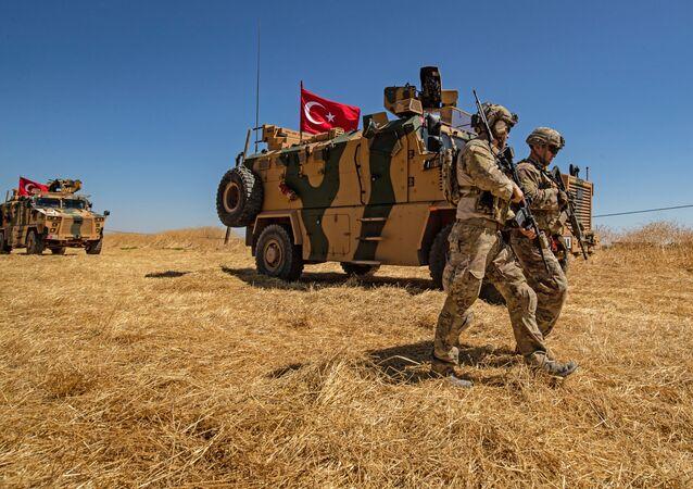 Amerykańscy żołnierze mijają turecki pojazd opancerzony na obrzeżach Tal Abyad