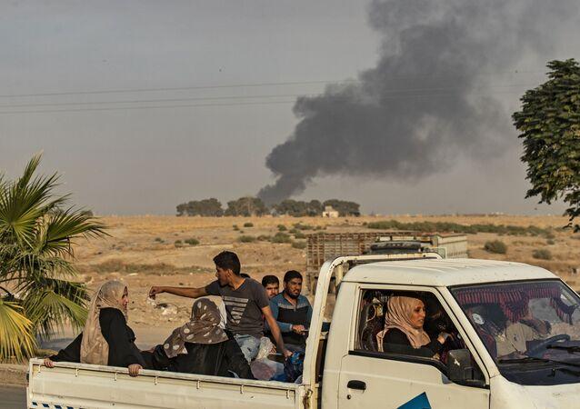 Arabscy i kurdyjscy cywile uciekają po bombardowaniu syryjskiego miasta Ras Al-Ajn przez Turcję