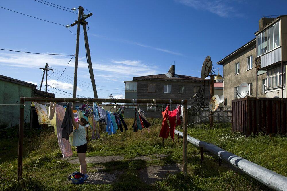 Kobieta wiesza pościel w centrum Jużno-Kurilska