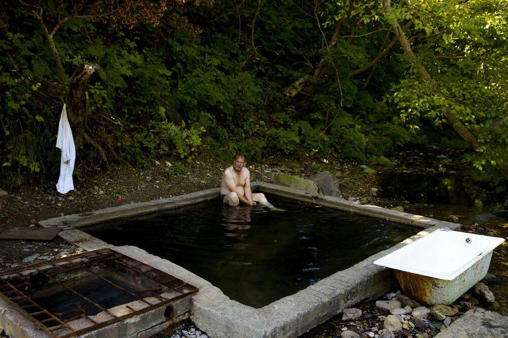 Mężczyzna na gorących źródłach niedaleko Jużno-Kurilska na wyspie Kunaszyr