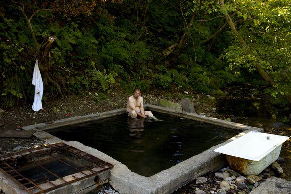 Mężczyzna na gorących źródłach niedaleko Jużno-Kurilska na wyspie Kunaszyr - Sputnik Polska