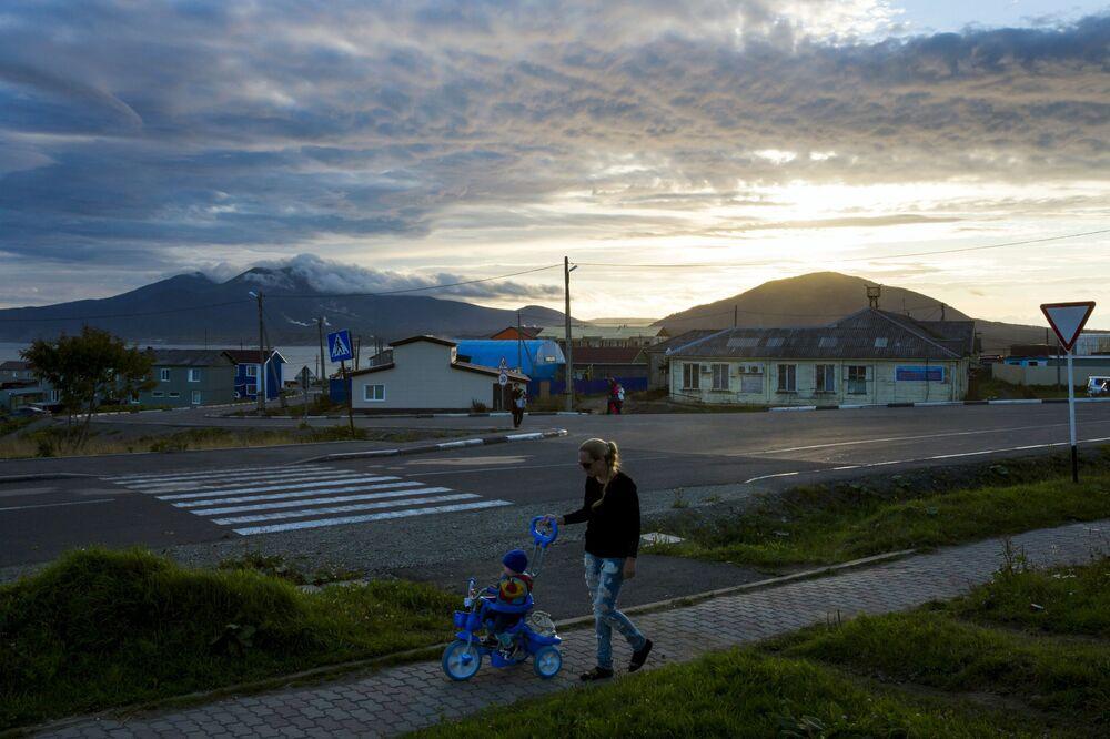 Kobieta spaceruje z dzickiem na zachodzie słońca w centrum Jużno-Kurilska na wyspie Kunaszyr