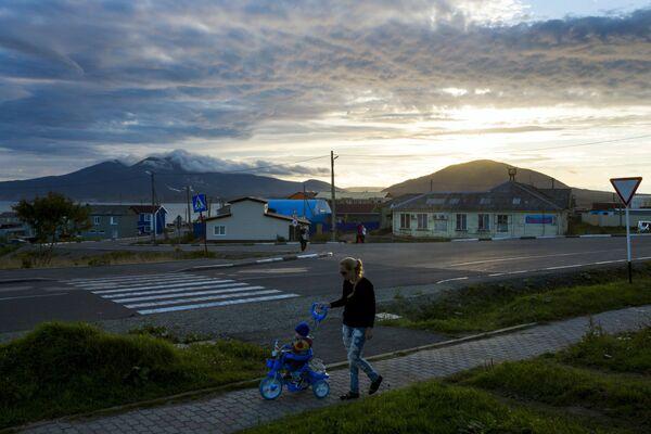Kobieta spaceruje z dzickiem na zachodzie słońca w centrum Jużno-Kurilska na wyspie Kunaszyr - Sputnik Polska