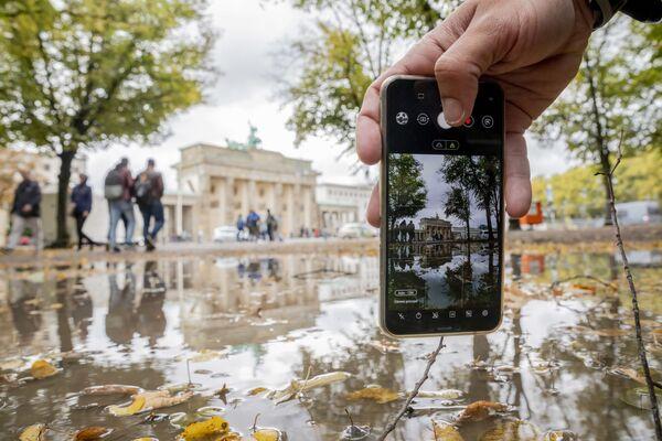 Mężczyzna fotografuje na telefon Bramę Brandenburską w Berlinie  - Sputnik Polska