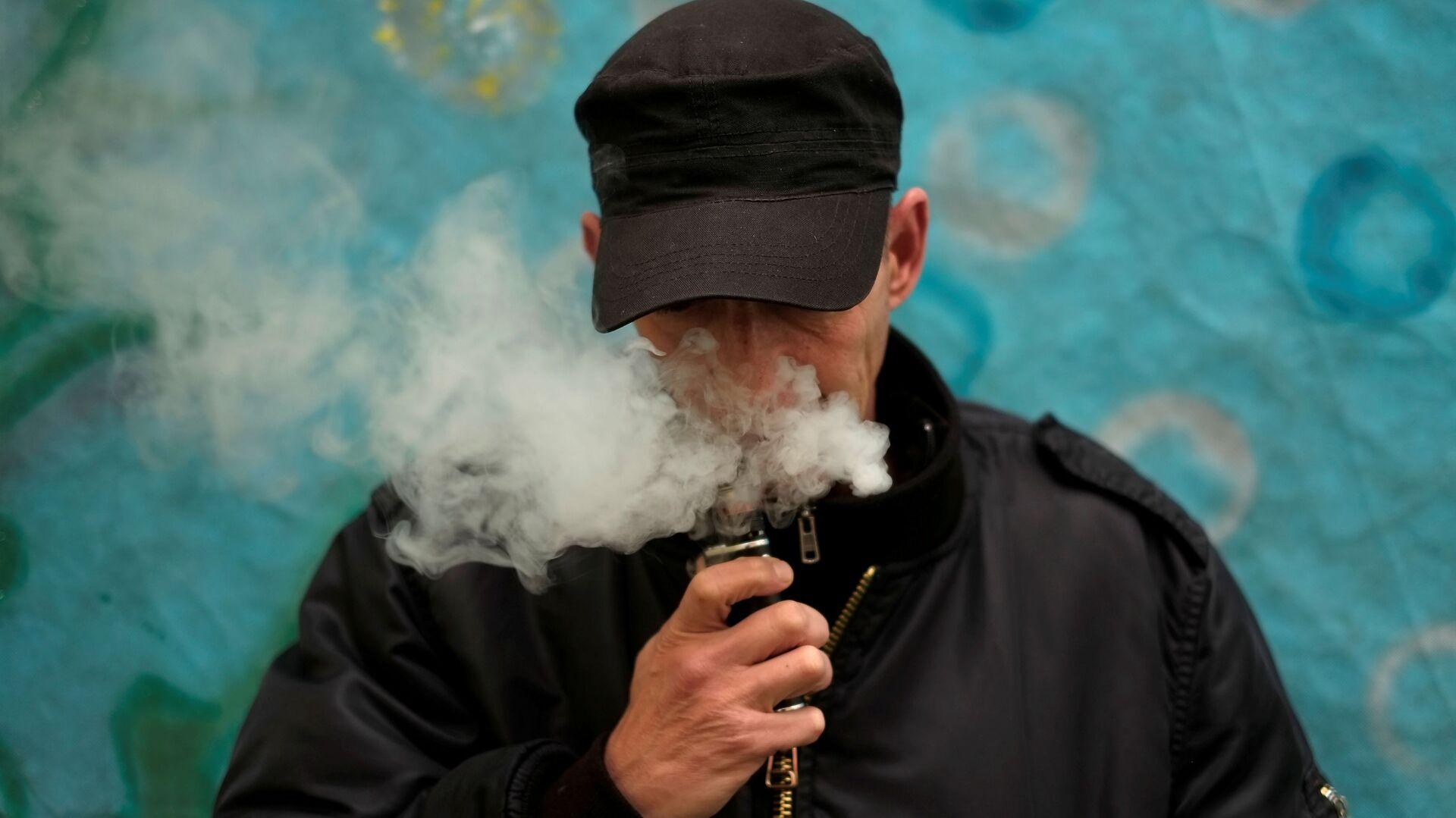 Mężczyzna pali elektronicznego papierosa - Sputnik Polska, 1920, 27.07.2021