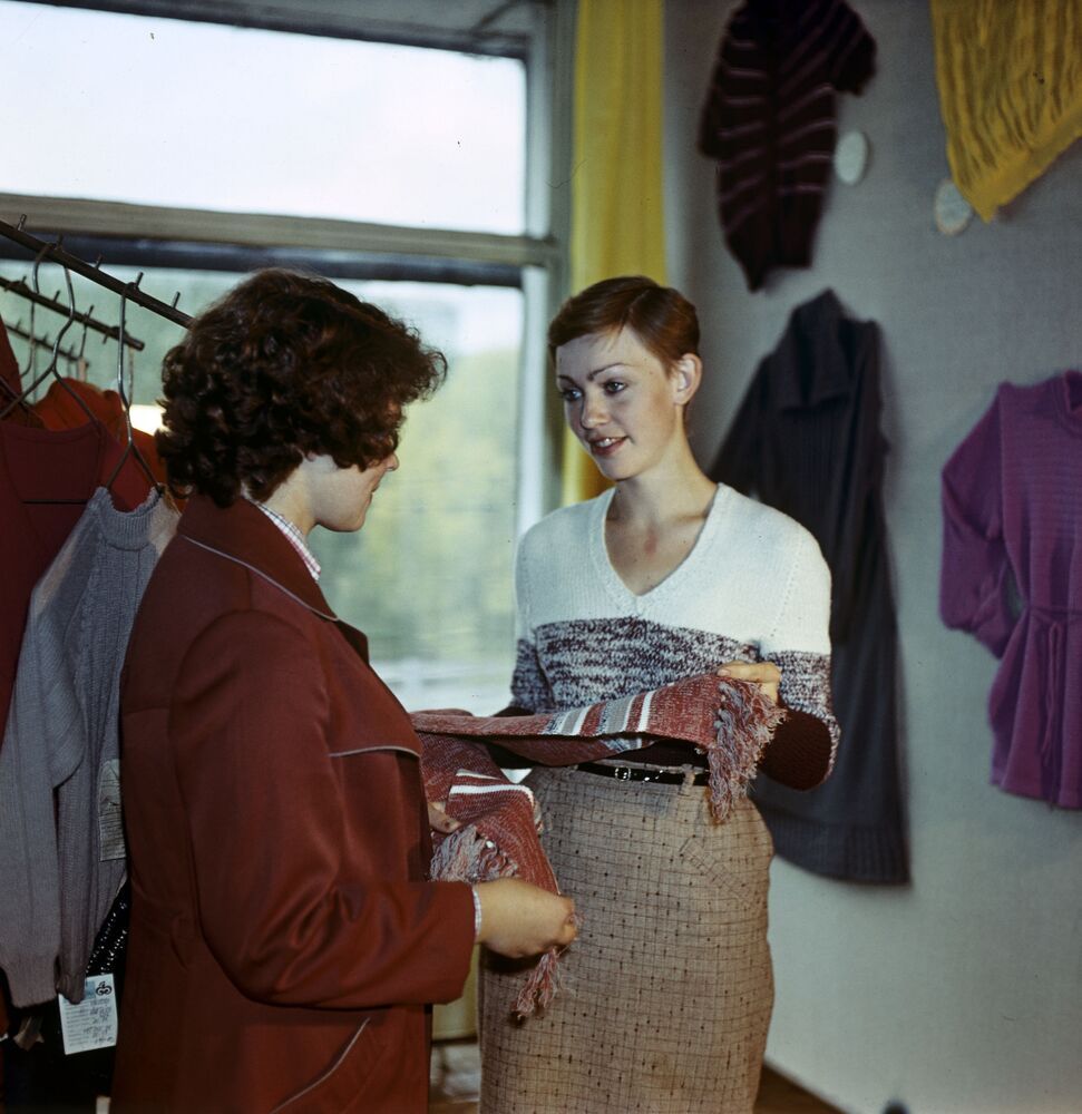 W salonie dzianin recepcjonistka pokazuje odwiedzającym gotowe produkty