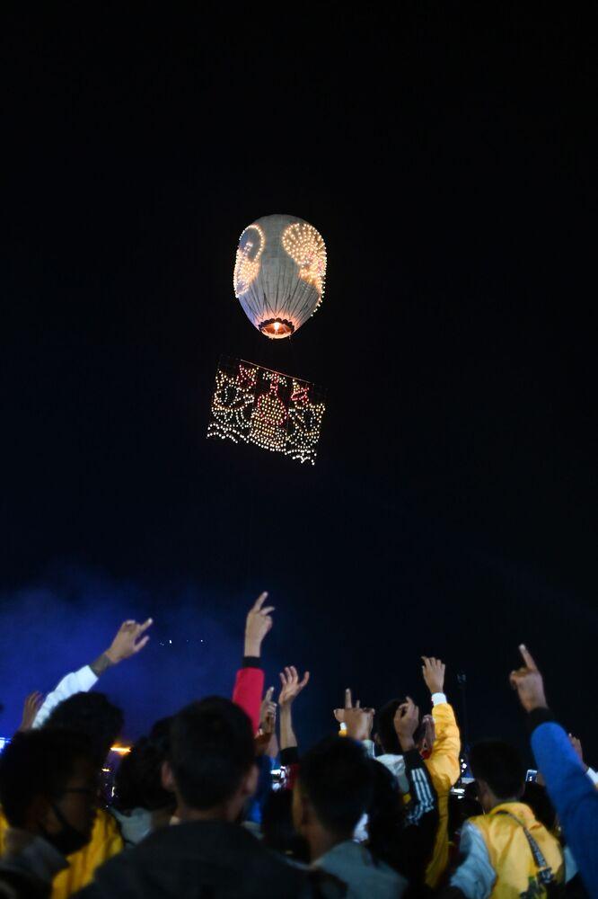 Puszczanie lampionu na festiwalu Tazaungdaing Lighting Festival w Mjanmie.