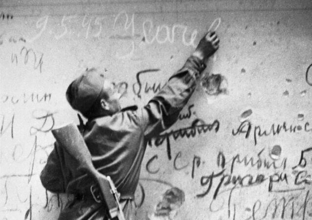 Radziecki żołnierz wykonuje pamiątkowy napis na ścianie Reichstagu