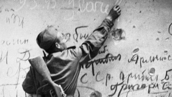 Radziecki żołnierz wykonuje pamiątkowy napis na ścianie Reichstagu - Sputnik Polska