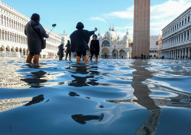 Turyści robią sobie zdjęcia na placu Św. Marka podczas powodzi w Wenecji